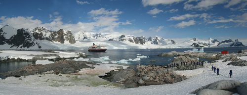 Antarctic tour boat, with visitor on land in foreground.