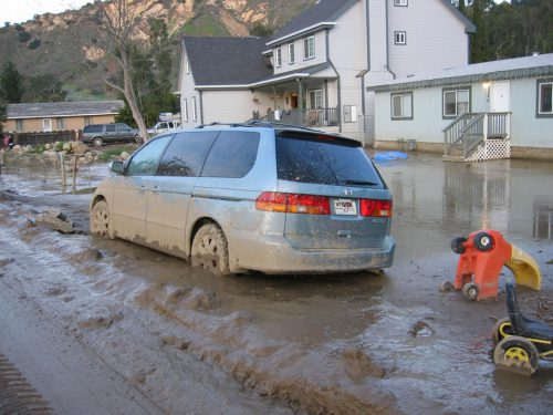 Car and houses surrounded by mud in mudslide - 2005.