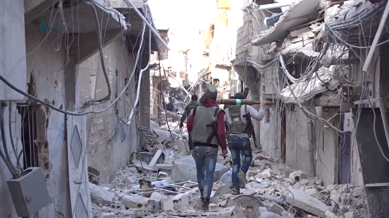Rebels in Damascus walk through bombed area, April 2017.
