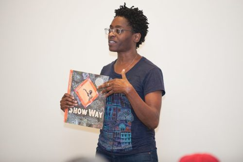 Author Jacqueline Woodson speaks, holding one of her books.