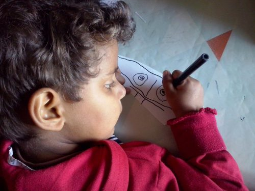 A child drawing with a pencil.