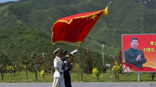 China flag waves in foreground, Xi Jinping on billboard in background