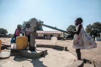 Children pump water in Mozambique.