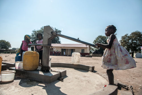 Children pump water in Mozambique.