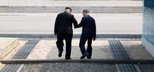 South Korean president Moon Jae In and Kim Jong Un, the leader of North Korea, step across the border between the two countries.