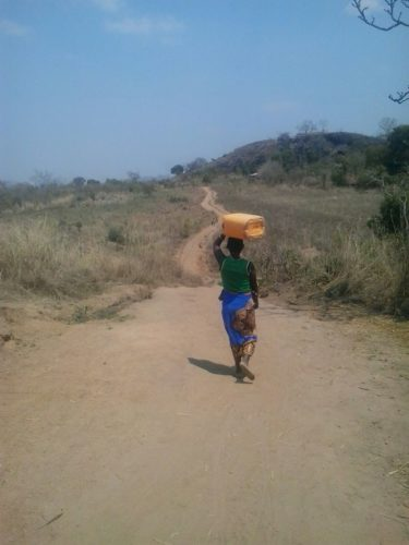 Woman walking to get water, Mozambique