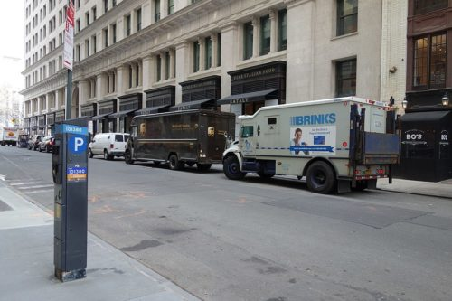 A Brink's armored truck and a UPS truck parked in Manhattan.