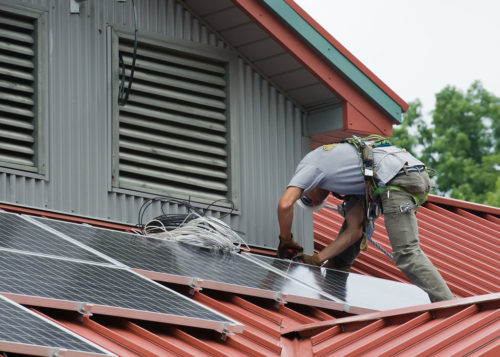 Installing solar panels on a roof.