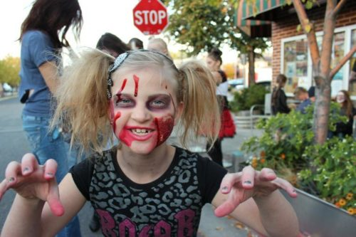 A young girl dressed up as a zombie for Halloween.