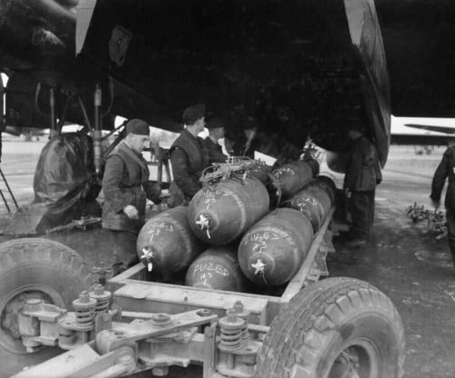 British soldiers loading 1,000 pound bombs into an airplane during World War II.