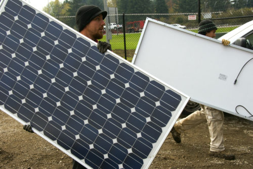 Men carrying solar panels for installation.