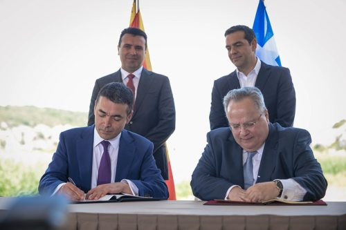 The prime ministers of Greece and Macedonia watch as the agreement is signed.