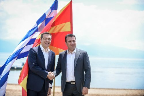 The prime ministers of Greece and Macedonia shake hands after the agreement is signed.