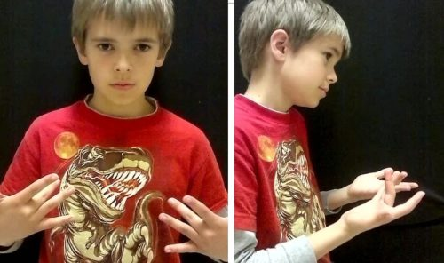 """A boy shows how to say, """"What's up?"""" in sign language."""
