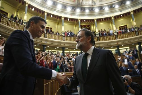 Pedro Sánchez (left) shakes hands with Mariano Rajoy (right).