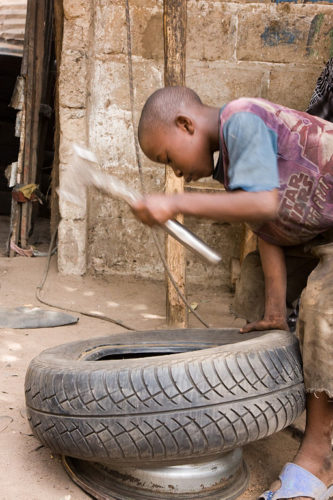 A child repairs a tire in The Gambia.