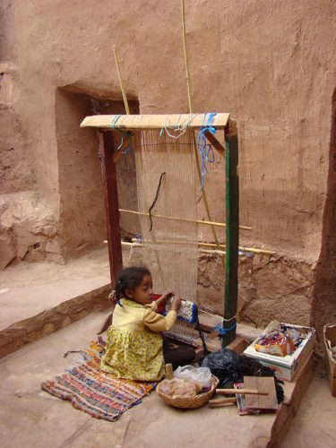 Young girl weaving in Morocco.