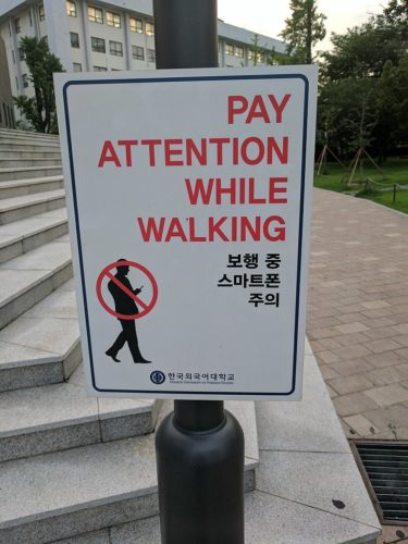 "Sign saying ""PAY ATTENTION WHILE WALKING"" in Seoul, Korea."