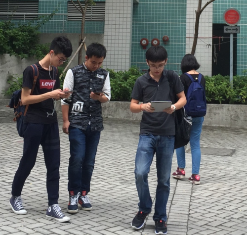 People staring at their smartphones while walking.