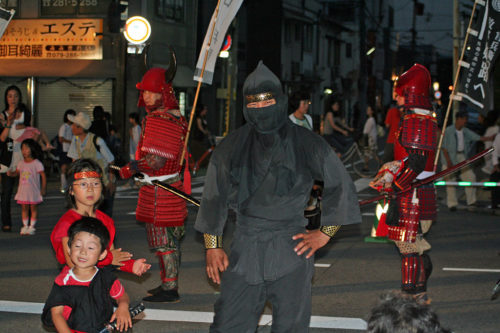 Ninja performer with kids at a festival.