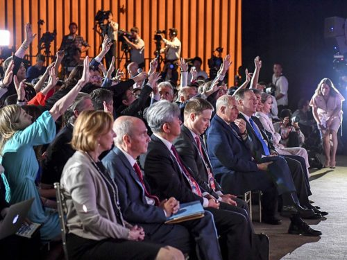 Reporters raise their hands to ask Mr. Trump a question.