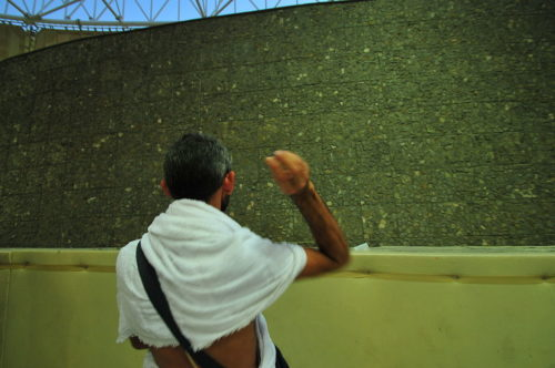 """Man throwing rock against stone wall as part of """"stoning the devil"""" during the hajj."""