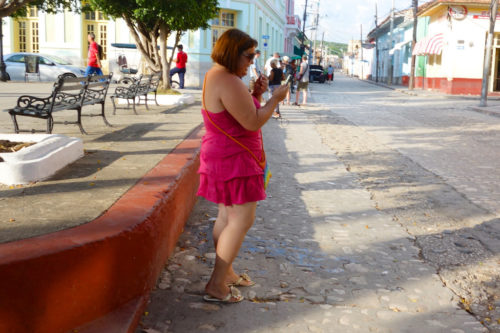 Woman in street looking at phone.