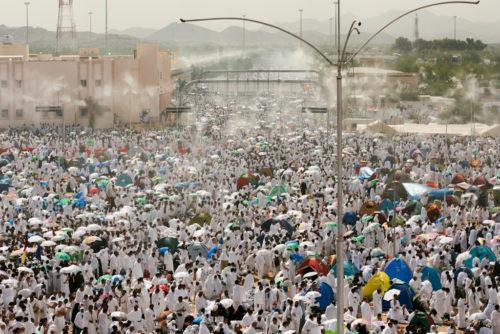 Crowds of hajj pilgrims being sprayed with mist.