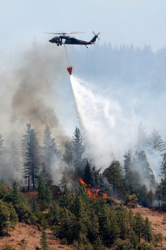 A California National Guard UH-60 Blackhawk crews drop water on the Ponderosa wildfires near Redding, Calif.