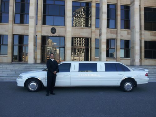 Chauffeur in front of white limoi