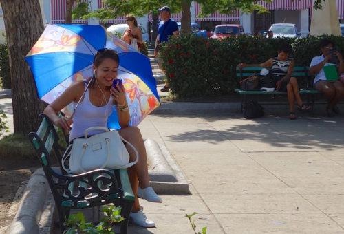 Girl on phone near plaza in Cuba.