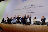 French Foreign Minister, UN Secretary-General Ban, and French President Hollande Raise Their Hands After Representatives of 196 Countries Approved a Sweeping Environmental Agreement at COP21 in Paris