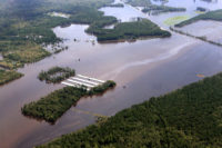 Flooded CAFO with a visible stream of pollution on the water's surface.