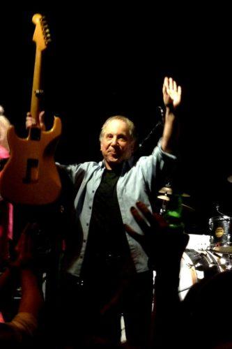 Paul Simon raising guitar in concert in 2011.