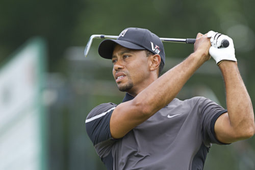 Tiger Woods watches the ball after finishing his swing. 2013