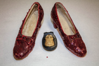 The recovered ruby slippers, along with an FBI badge. The single sequin shown here was found at the crime scene at the Judy Garland Museum, from which a pair of Ruby Slippers went missing in 2005.
