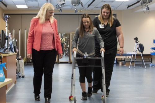 Paralyzed woman walks using a walker.
