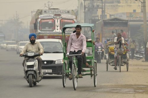 A variety of vehicles on a hazy and busy street. Pic by Neil Palmer (CIAT). GV of traffic in Sangrur, SE Punjab, India.