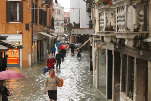 Pedestrians walking through flood tide waters in Venice in 2012.