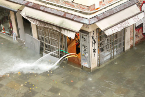 Water being pumped out of a flooded shop, Venice, 2012.