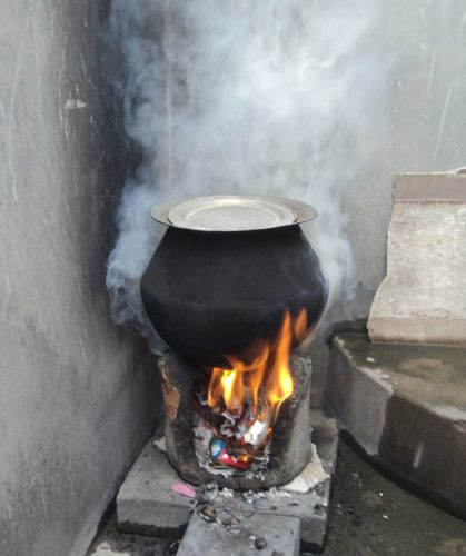 A rural stove using biomass cakes, fuelwood and trash as cooking fuel.