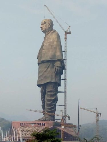 Picture of Statue of Unity under construction with cranes at work.