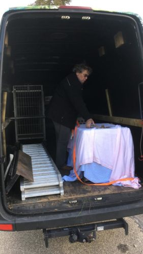 Man standing in back of an open van next to a covered cage.
