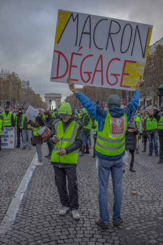 Protester holding a sign saying, Macron Degage, with Arc de Triomphe in background