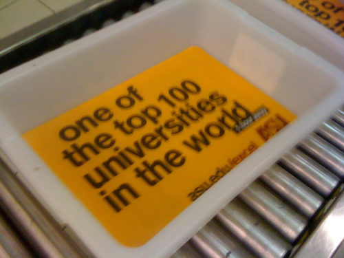 Picture of TSA bin with big yellow advertisement.