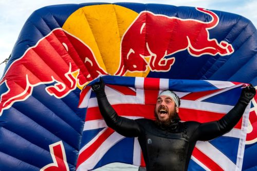 Ross Edgley holds a British flag behind him at the end of his 157 day swim around the UK.