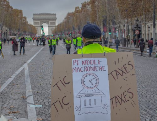 "Man carrying a sign with a clock and the words ""Tic-taxes, tic-taxes"", with the Arc de Triomphe in the background."