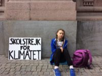 "Greta seated with backpack. On the left is her sign in Swedish, which says, ""School Strike for Climate""."