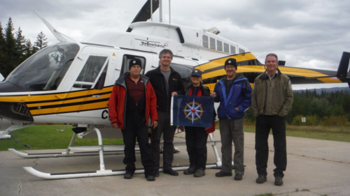 Team holding the Royal Canadian Geographical Society Flag after successfully completing the reconnaissance work. Left to right: John Pollack, Ken Lancour (Yellowhead Helicopters), Catherine Hickson (Tuya Terra Geo Corp.), Lee Hollis (Cody Cave), Tod Haughton (BC Park Official) (photo by self timer – John Pollack's camera)
