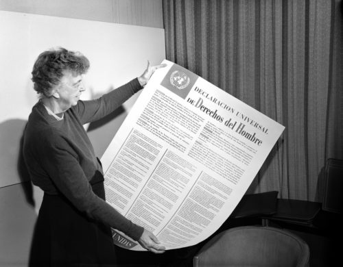 Eleanor Roosevelt of the United States holding a Universal Declaration of Human Rights poster in Spanish.